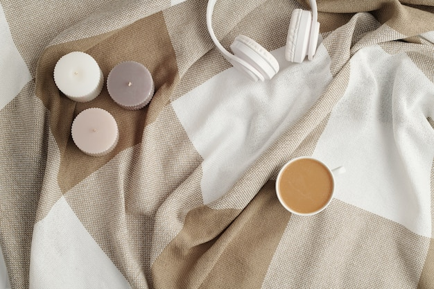 Flat lay of three small aromatic candles, white headphones and cup of fresh cappuccino on checkered linen or cotton plaid