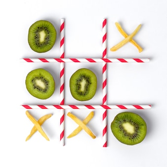 Flat lay tic tac toe made of kiwi, fries and straws.