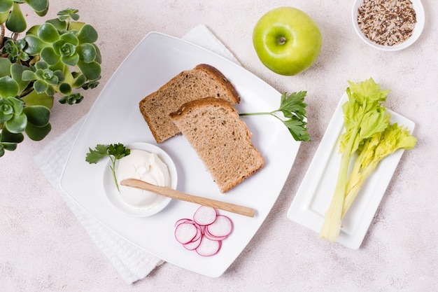 Flat lay of toast on plate with radish and apple