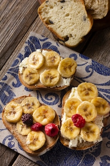 Flat lay toast with bananas and forest fruits