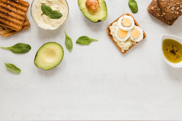 Flat lay toast with hummus eggs and avocado with copy space