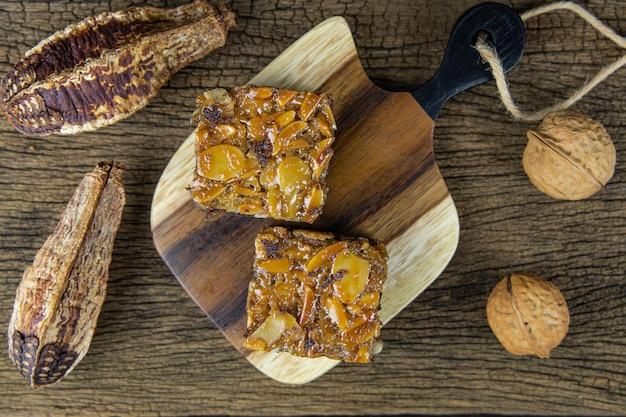 Плоские кладут квадраты торта ириски на деревянный поднос и на стену деревянного стола.
