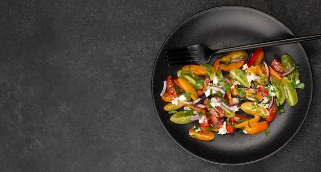 Плоский салат-микс из помидоров с сыром фета, рукколой и копировальным пространством