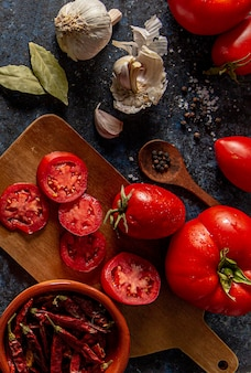 Flat lay of tomatoes with garlic and bay leaves