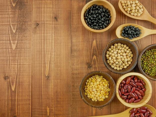 Flat lay, top view assorted beans including red bean, soybeans, black beans, mung beans on brown, beige wooden background