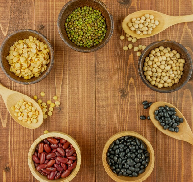 Flat lay, top view assorted beans on wooden table with copy space