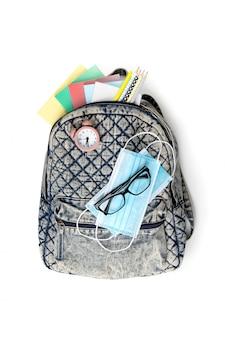 Плоский лежал рюкзак с видом сверху с различными красочными канцелярскими принадлежностями на белом столе. снова в школу концепции