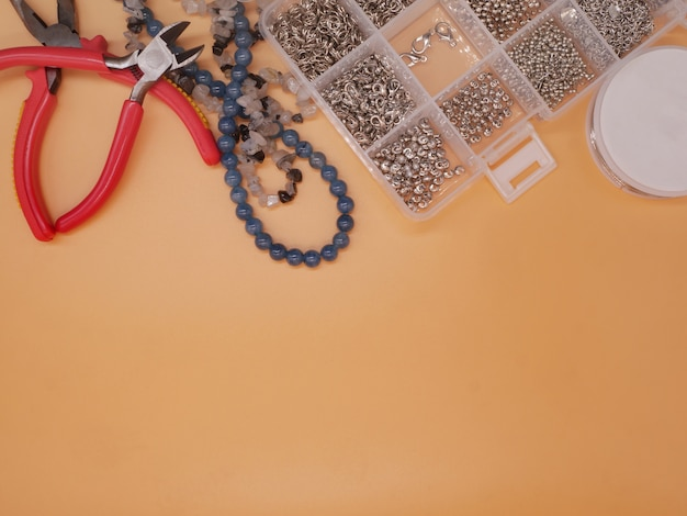 Flat lay, top view beading supplies on orange background