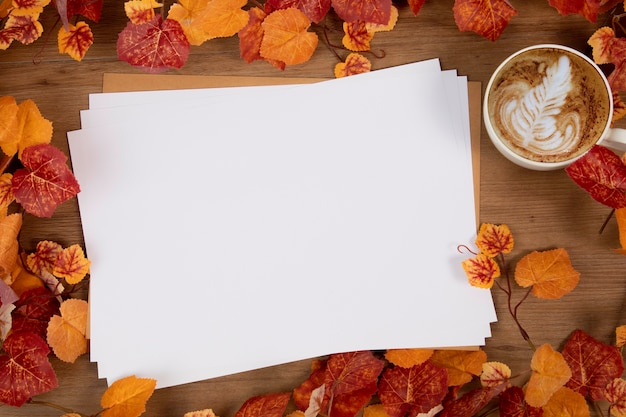 Flat lay top view of blak letter paper and autumn leaves