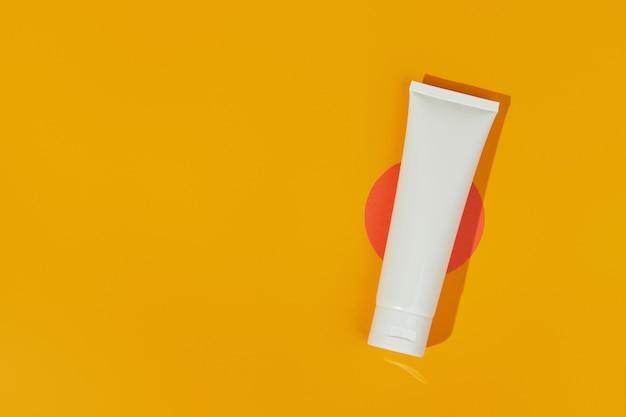 オレンジ色の背景にローションクリームまたはクレンザーとフラットレイトップビュー空白の白いチューブボトル