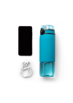 Flat lay top view blue bottle of water, headphones and smartphone isolated on white background