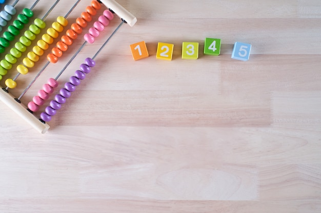 Flat lay, top view of bright colored wooden bricks and abacus toy background with copy space for text