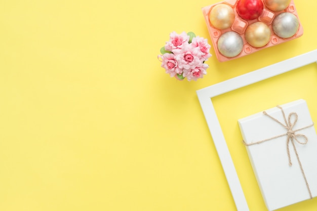 Flat lay top view colorful easter egg painted in pastel colors composition and spring flowers