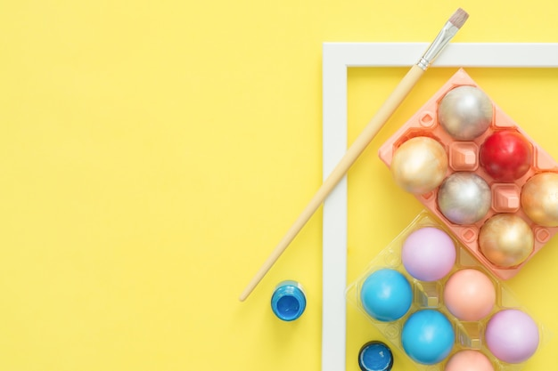 Flat lay top view colorful easter egg painted in pastel colors composition with paintbrush