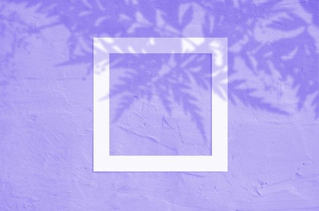 Flat lay top view of creative copyspace with paper frame and tropical leaves palm shadow on violet color background.
