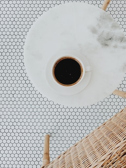 Flat lay, top view of cup of coffee on white round marble table