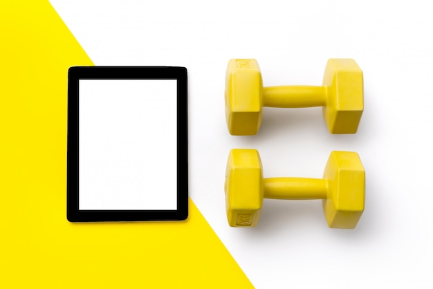 Flat lay top view dumbbells and tablet on white and yellow double background