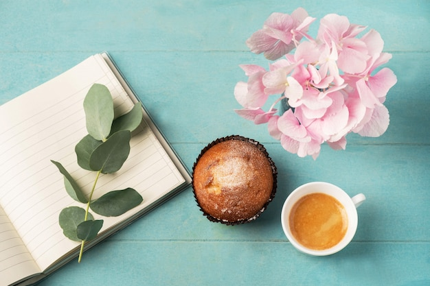 Flat lay, top view of feminine desk. coffee cup for breakfast, cupcake, empty notebook, branch with eucalyptus leaves and and pink hydrangea. business planning breakfast concept.