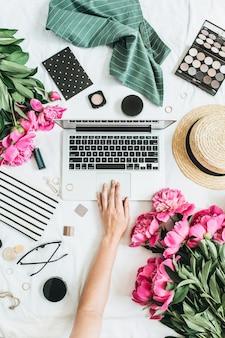 Плоская планировка, вид сверху женственного рабочего места за офисным столом с ноутбуком, цветами пиона, очками, соломенной шляпой, косметикой, аксессуарами. женщина, работающая на компьютере.