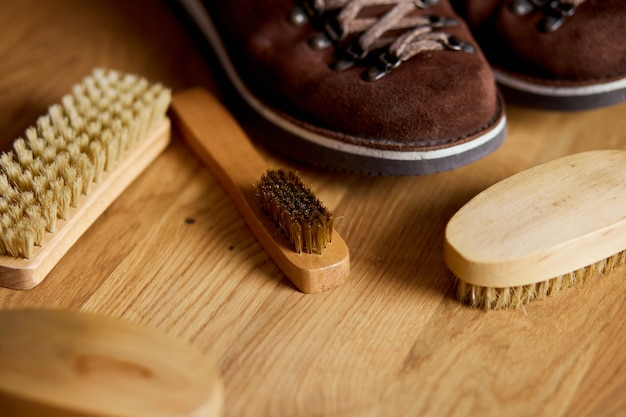 Flat lay, top view footwear with suede shoe boots care accessories, brush on wooden table.