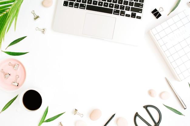 フラットレイ、オフィステーブルデスクのトップビューフレーム。ノートブック、ラップトップ、椰子の枝、コーヒーカップ、はさみ、白い背景のクリップとワークスペース。