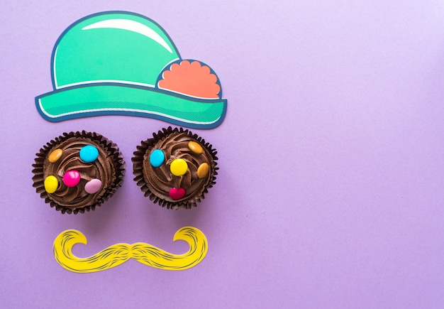 Flat lay top view of funny face made of party preparation accessories and two muffins