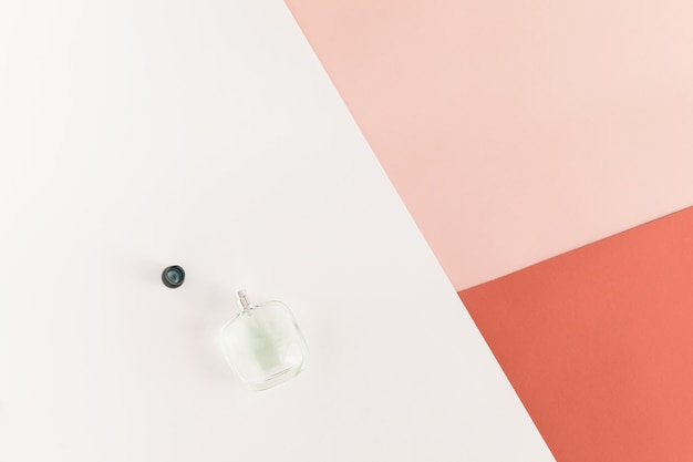 Flat lay and top view of glass perfume bottle on white pink coral desk