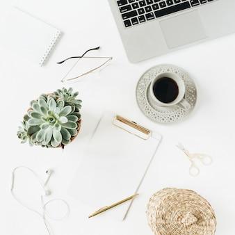 クリップボード、ラップトップ、コーヒー、白地に文房具を備えたフラットレイ、トップビューのホームオフィスデスクワークスペース