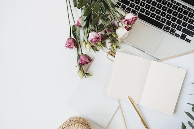 白いテーブルの上に白紙のノートブックとラップトップを備えたフラットレイ、トップビューのホームオフィスワークスペース
