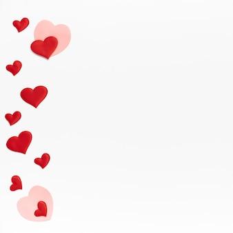 フラットレイ、上面図。白い孤立した背景に多くの小さな色のハート。テキストの場所とバレンタインデーのテンプレート