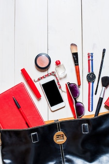 Flat lay, top view, mock up cosmetics and women's accessories fell out of the black handbag on white background. phone, glasses, watch, notebook, pen