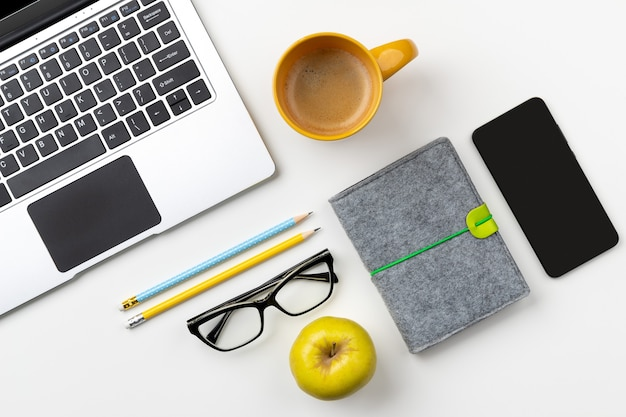 Flat lay top view modern laptop food and stationery on white table