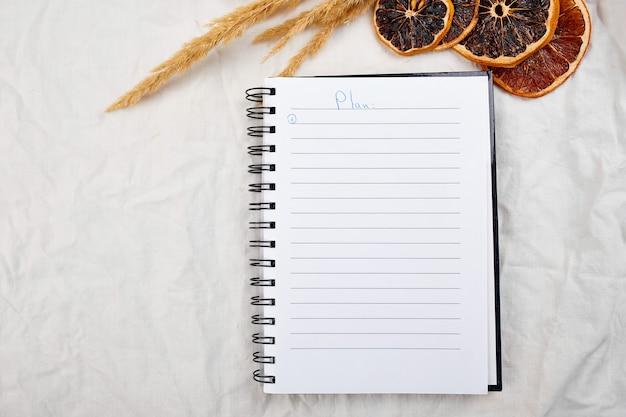 평평한 평면도 노트북, 식탁보 배경에 팜파스 풀이 있는 메모, 삶의 목표 및 계획