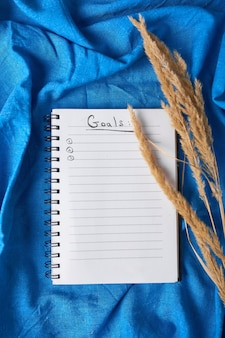 Flat lay top view notebook, notes with pampas grass on tablecloth background, life goals and plan Premium Photo