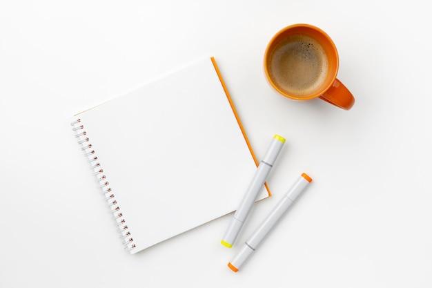 Плоский лежал сверху блокнот, маркеры и чашка кофе на белом столе