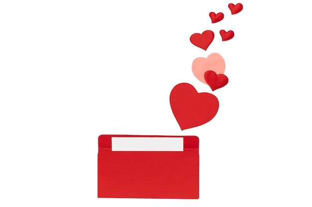 フラットレイ、白い孤立した背景に多くの小さなハートとその中に文字が入った赤い封筒の上面図