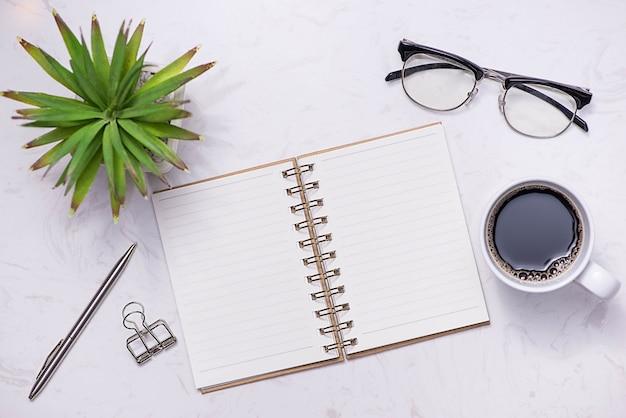 Плоская планировка, вид сверху открытой записной книжки и других принадлежностей.