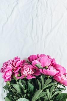 フラット レイアウト、白い毛布の背景にピンクの牡丹の花の花束のトップ ビュー