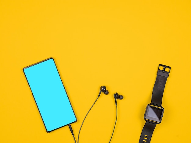 Плоский вид сверху смартфона и умных часов. дизайн и концепция. оранжевый фон