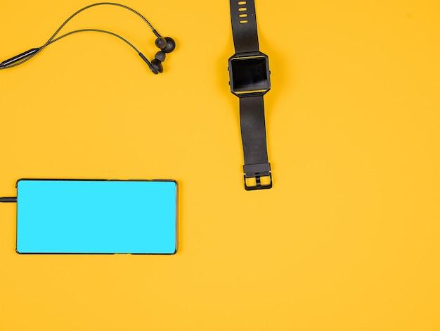 Плоский вид сверху смартфона с наушниками и умными часами. дизайн и концепция. оранжевый фон