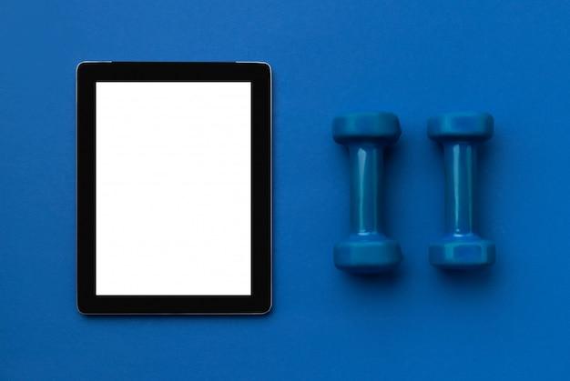 Плоский вид сверху планшета со спортивным оборудованием на классическом синем фоне. концепция фитнеса здорового образа жизни онлайн