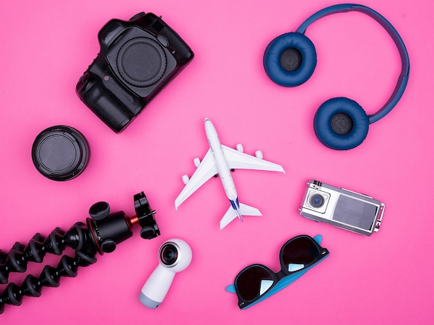 분홍색 배경에 여행자 사진가 액세서리의 평평한 평면도. 삼각대 헤드폰. 색안경