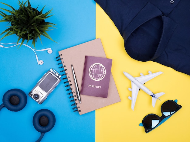 노란색 배경에 여행자 사진가 액세서리의 평평한 평면도. 카메라, 선글라스, 여권. 공책 . 셔츠