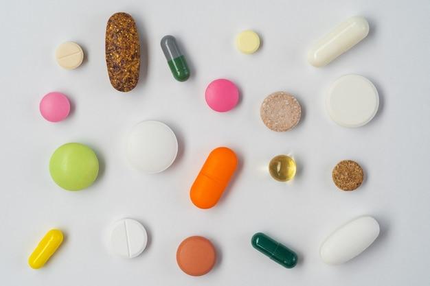 Плоская планировка (вид сверху) различных типов таблеток, таблеток и капсул, изолированных на белой стене.