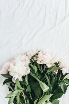 Плоская планировка, вид сверху букет цветов белых пионов на поверхности белого одеяла