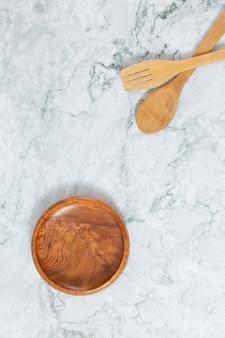 Плоские лежал вид сверху деревянные ложки, узор деревянный диск на мраморном столе.