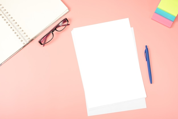 Flat lay, top view office desk. blank paper, eyeglasses, notepad, note paper on pink table.