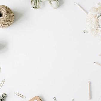 평면 위치, 최고보기 사무실 테이블 책상. 꼬기, 연필, 꽃 꽃다발, 공예 일기 및 흰색 배경에 클립과 여성 책상 작업 영역 프레임.