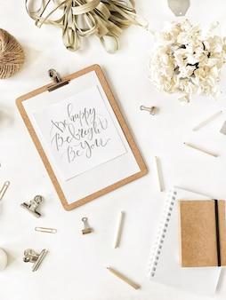 평면 위치, 최고보기 사무실 테이블 책상. 클립 보드 및 영감 따옴표, 꼬기, 연필, 꽃 꽃다발, 공예 일기 및 흰색 배경에 클립이있는 여성 책상 작업 공간.