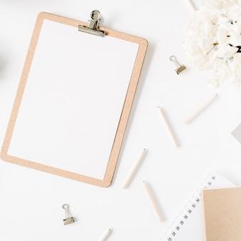 평면 위치, 최고보기 사무실 테이블 책상. 클립 보드, 꼬기, 연필, 꽃 꽃다발, 공예 일기 및 흰색 배경에 클립과 여성 책상 작업 공간.